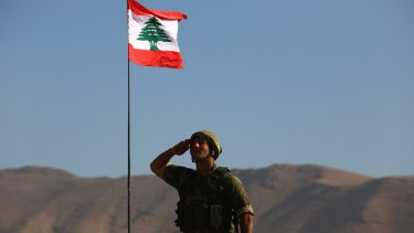 A Lebanese soldier salutes the national flag atop an armoured personnel carrier on the outskirts of Ras Baalbek, north-east Lebanon.