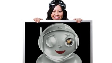 Le wearing the original EPOC headset that senses her smile and wink, causing a computer-generated cartoon robot to mirror her expression.