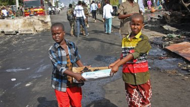 Somali children assist other civilians and security forces in their rescue efforts by carrying away unidentified charred human remains in a cardboard box, to clear the scene of the blast.