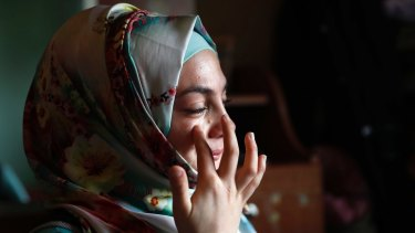 Alaa, 19, who was shot in March 2013 in her jaw during clashes between Syrian government forces and rebels  in the Syrian province of Homs, wipes tears as she tells her  story in Bebnine town, northern Lebanon.