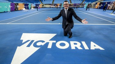 Premier Daniel Andrews poses with the new logo for Victoria.