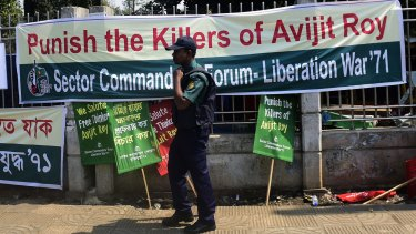 A Bangladeshi policeman walks past a banner for slain US blogger Avijit Roy during a protest in Dhaka.