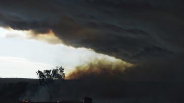 Farmers battle a lightning strike fire which was started by the mammoth blaze west of Cassilis.