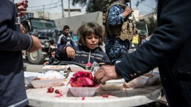 A girl eats food distributed by volunteers in west Mosul.