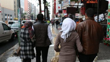 The couples walk along the street in the Turkish city of Izmir, where supplies for the Aegean Sea crossing are sold.