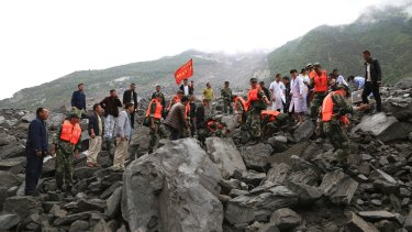 Emergency personnel work at the site of a landslide in Xinmo village on Saturday.