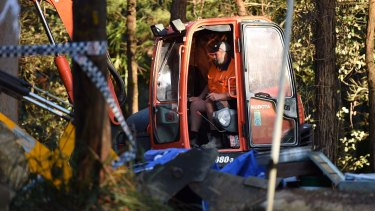 A man operates the digger at the scene in the Royal National Park at Waterfall where Matthew Leveson's remains were unearthed.