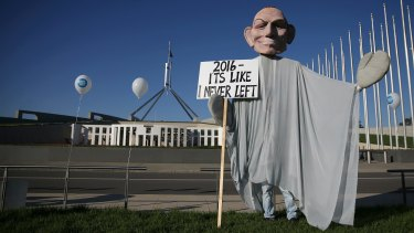 A man in a 'ghost of Tony Abbott' costume at the rally to save CSIRO jobs on the front lawn of Parliament House.