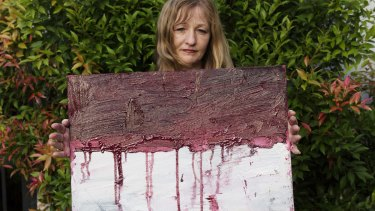 Sukumaran's painting teacher Tina Bailey holds a painting of the Indonesian flag dripping with blood, created on the day before his execution.