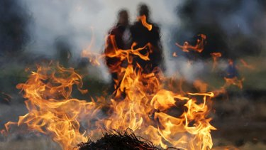 Family members stand next to the burning pyre of a family member at a cremation ground in Bhaktapur, Nepal. The death toll is now over 4100.