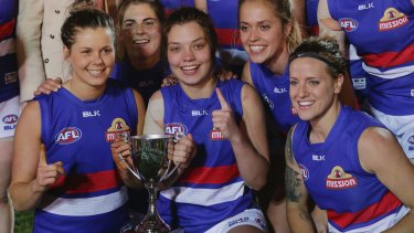 Meg Hutchins of the Bulldogs (centre) and teammates after winning the AFL Women's Exhibition Match last Saturday.
