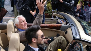 Australia's only James Bond, George Lazenby, waves to fans during the SpyFest Street Parade on Saturday.