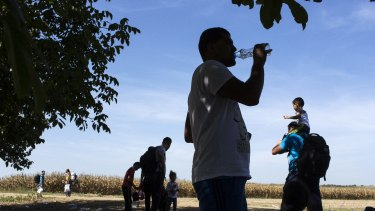 Refugees stop for a break during the midday heat on their way to the border crossing from Serbia into Tovarnik, Croatia, on Thursday.