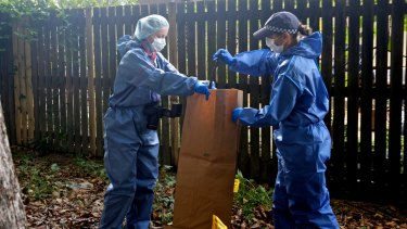 Police collect metal bar from the park next to the home where eight children were killed.