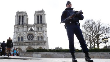 A French police officer stands guard outside Notre Dame cathedral in Paris earlier this year.