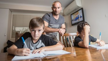 Craig Zammit helps his sons Thomas and Mason with their homework.