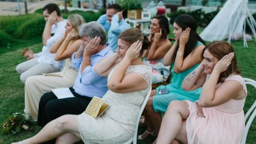 Not just between a man and a woman: Friends and family join in the protest at the Johnstons' wedding.