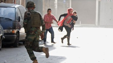 A Lebanese soldier runs past fleeing residents during the clashes in Tripoli, the country's second city, between Lebanese forces and Islamist gunmen.