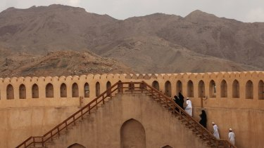 Omanis climb the wall of the Nizwa Fort, west of the capital Muscat. The fort was once Oman's seat of government.