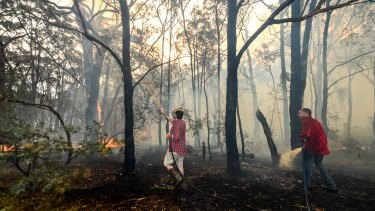 Adam Watkins and partner Prue Mathiesen fight the fire to save their home in Lancefield.