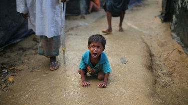 A Rohingya child cries on the ground at a makeshift refugee camp in Bangladesh. Children have given harrowing accounts of violence in Myanmar.
