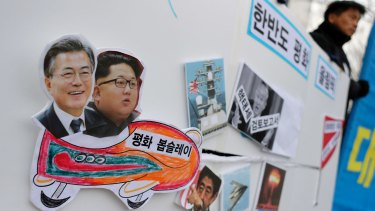 A South Korean protester holds a sign with pictures of President Moon Jae-in, left, and North Korean leader Kim Jong-un, second left, during a rally to denounce the US policy against North Korea and demand a peaceful Winter Olympics.