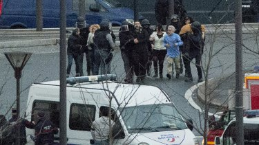 Security officers escort released hostages after they stormed a kosher market to end a hostage situation.