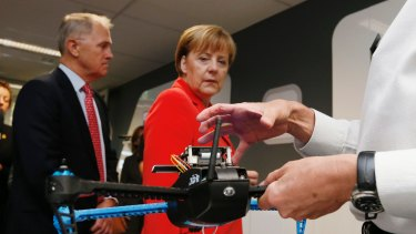 Germany's Chancellor Angela Merkel looks at a drone prototype during a tour of NICTA's Future Logistics Living Lab.
