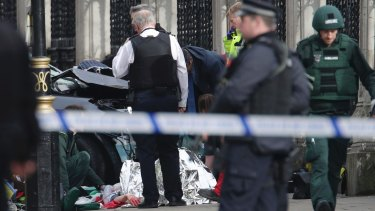 Emergency personnel tend to an injured person close to the Palace of Westminster, London.