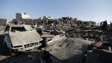 People gather at the site of an air strike in Yemen's capital, Sanaa.