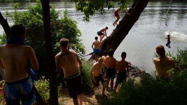 Kids cool off on the rope swing at Tench Reserve, Penrith, as the mercury nears 38 degrees.