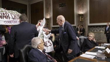 Former US secretary of state George Shultz stands to move protesters away from Henry Kissinger.