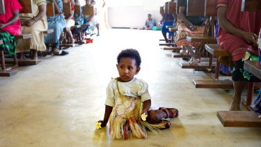 A girl sits it the aisle of the Catholic church during Mass on Manus Island, Papua New Guinea, in 2013. The church is one of the major providers of health care in PNG's remote communities.
