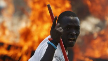 A protester stands in front of a burned barricade during a protest against Burundian President Pierre Nkurunziza's decision to run for a third term in Bujumbura, Burundi on Wednesday.