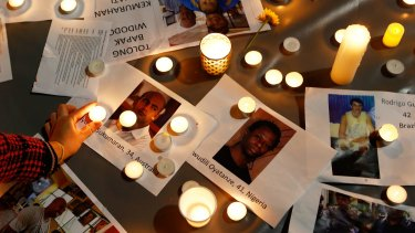 A woman places a candle on top of pictures of the prisoners at a vigil in Sydney on Tuesday night ahead of the executions in Indonesia.