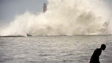 A man walks on a sea wall as the ocean crashes into el Morro lighthouse, after the passing of Hurricane Irma in Havana, Cuba.