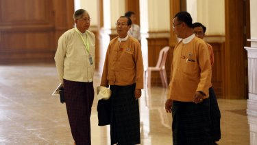 Htin Kyaw, left, a National League for Democracy presidential candidate, speaks with NLD MPs in parliament on Monday.