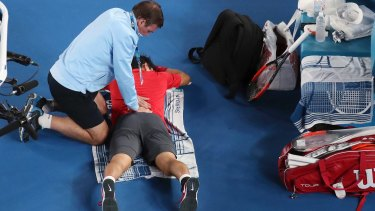 Kei Nishikori, laying down, is treated by a trainer during a break in play.
