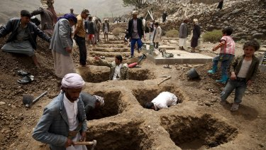 People dig graves for the victims of an air strike in Okash village near Sanaa on Saturday.