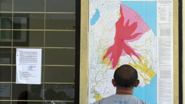 A man observes a map of the Mount Agung volcano at the Mount Agung monitoring station.