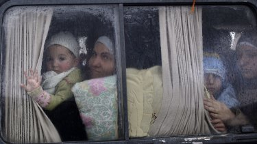 Syrian refugees cross the border from Syria to Turkey on a bus.