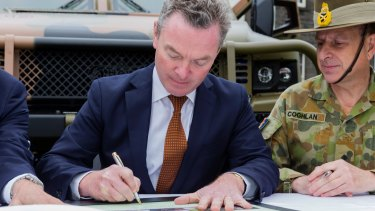 Minister for Defence Industry Christopher Pyne signs the acceptance of the last two Hawkei Pilot vehicles at a ceremony at Victoria Barracks last year.
