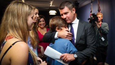 Mike Baird embraces his family after resigning as premier on January 19.