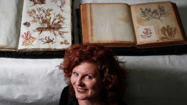 Julie Ryder with the two rare seaweed albums that will go on display at the National Museum of Australia in April.