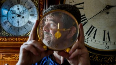 Master clockmaker: Andrew Markerink in his workshop with antique clocks and watches.