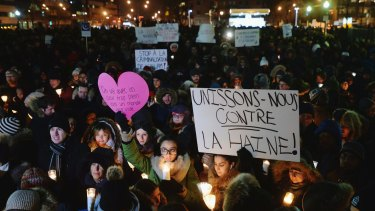 """People attend a vigil in Montreal for victims of Sunday's shooting at a Quebec City mosque. Sign reads """"let's unite against hatred""""."""