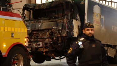 A destroyed truck is towed away after it was driven into a department store in Stockholm on Friday.