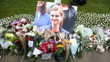 Flowers surround a photograph of British MP Jo Cox. Her death is almost forgotten in the social media storm about how to characterise her attacker.
