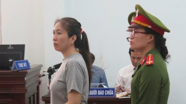 Prominent blogger Nguyen Ngoc Nhu Quynh, left, stands trial in Vietnam in June.
