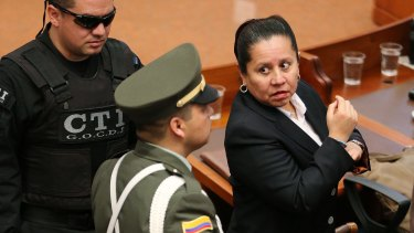 Maria del Pilar Hurtado (right), former head of Colombia's domestic intelligence agency, is escorted by judicial police into the Colombian Supreme Court to receive her sentence.